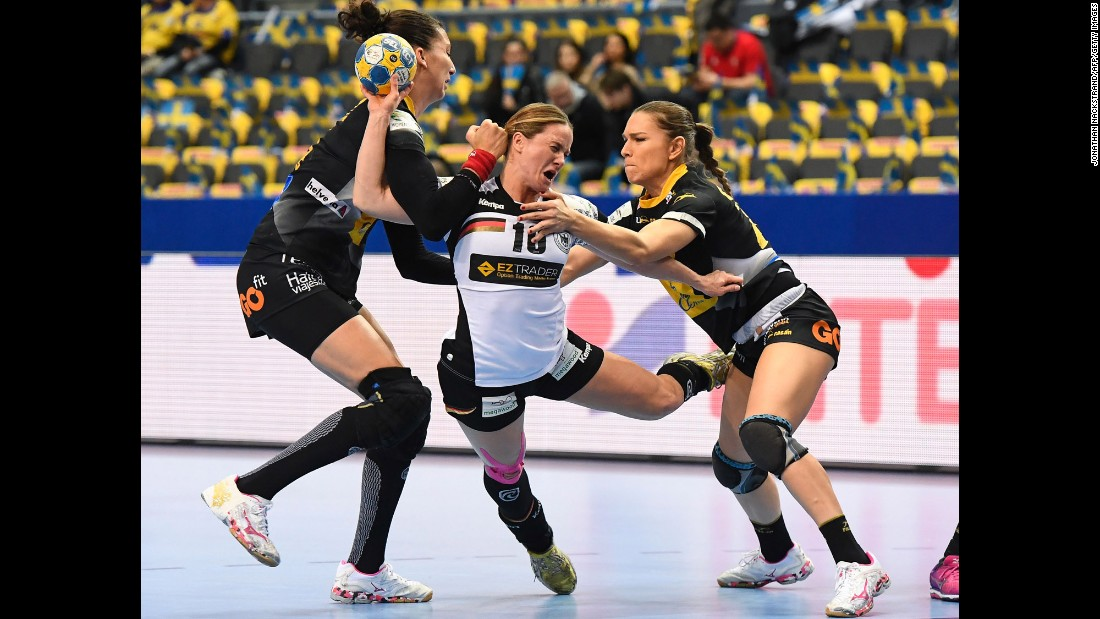 Spanish handball players Elizabeth Chavez, left, and Judith Sans try to stop Germany's Anna Loerper during a European Championship match in Gothenburg, Sweden, on Monday, December 12. The match ended 20-20.