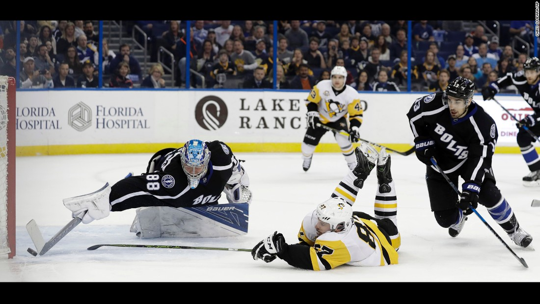 Pittsburgh captain Sidney Crosby slides on the ice as he scores a goal past Tampa Bay goalie Andrei Vasilevskiy on Saturday, December 10. Crosby had two goals in the 4-3 victory.