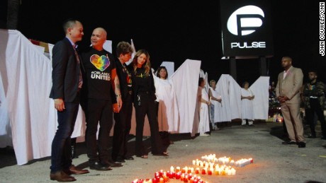 For the  6 month anniversary since massacre at Orlando's Pulse nightclub where 49 died the gates were opened around the club for a ceremony which included angels from the local theater community with candles for those killed. Hugs were given everywhere.