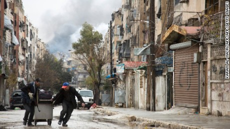 Smoke is seen billowing in the background on December 14, 2016 in this picture taken in a rebel-held neighbourhood in the northern city of Aleppo.  Deadly clashes erupted in Syria's Aleppo as a deal for the evacuation of rebel areas was put on hold, leaving thousands of cold and hungry civilians uncertain of their future  / AFP / KARAM AL-MASRI        (Photo credit should read KARAM AL-MASRI/AFP/Getty Images)