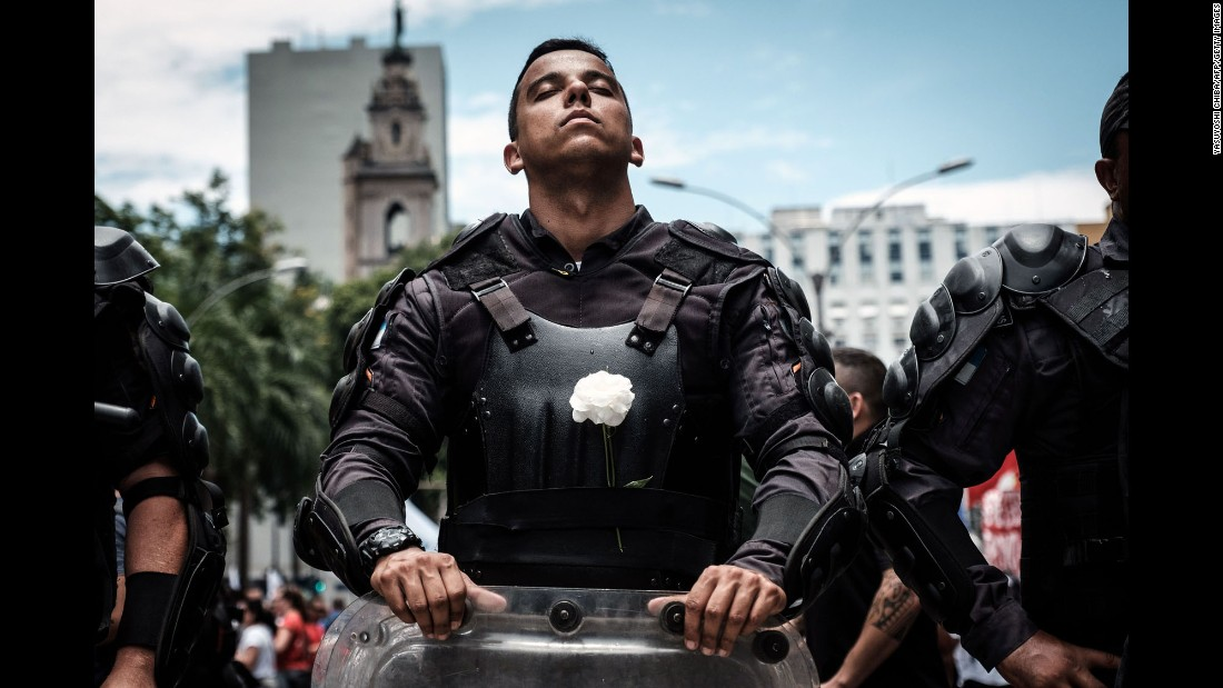 A police officer wears a white flower on his bulletproof vest while participating in a public servants' protest against the austerity measures in front of the State Assembly in Rio de Janeiro on Monday, December 12, as lawmakers began the voting measures.