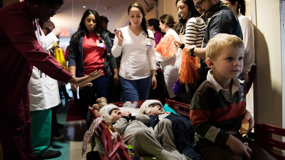 Jadon, left, and Anias McDonald look up at hospital staff as they leave their room at Montefiore Children's Hospital in New York. Their older brother, Aza, proudly sits at the front of the wagon. It was mid-December and they were headed to rehab.