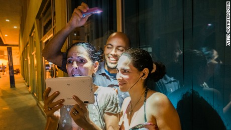 Leonor Cuza Tamayo, 52, chats with a sister in Miami as her son, Jose Luis Rodriguez, 33, holds a light over her head.