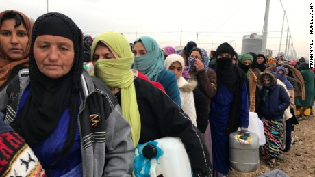 Hundreds spend their day lining up for supplies; it is cold, and people's patience is wearing thin.
