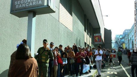 "People queue up outside a bank in San Cristobal in an attempt to deposit money, on December 13, 2016.  Venezuelan President Nicolas Maduro ordered on December 12 the border with Colombia sealed for 72 hours, accusing US-backed ""mafias"" of conspiring to destabilize his country's economy by hoarding bank notes. The closure came a day after Maduro signed an emergency decree removing Venezuela's largest bank note, the 100 bolivar bill, from circulation because of what he called a Washington-sponsored plot against his country's troubled economy. / AFP / George CASTELLANOS        (Photo credit should read GEORGE CASTELLANOS/AFP/Getty Images)"