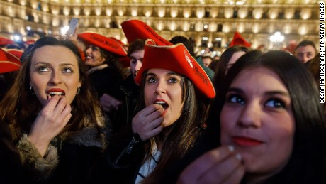 Students eat grape gummies while celebrating the traditional year-end party held in the main square of Salamanca, Spain on December 15, 2016.  The student end of year party has been celebrated every year since the 1990s in the main square of Salamanca in northern Spain, and this year's version drew 35,000 university students on December 15, 2016. / AFP / CESAR MANSO        (Photo credit should read CESAR MANSO/AFP/Getty Images)
