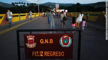 "People cross the Simon Bolivar bridge in Norte de Santander department, Colombia in the border with Venezuela, on December 11, 2016. Venezuelan President Nicolas Maduro on Sunday signed an emergency decree ordering the country's largest banknote, the 100 bolivar bill, taken out of circulation to thwart ""mafias"" he accused of hoarding cash in Colombia. / AFP / SCHNEYDER MENDOZA        (Photo credit should read SCHNEYDER MENDOZA/AFP/Getty Images)"