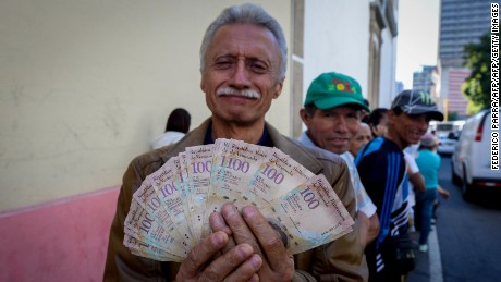 A man shows 100 Bolivar notes whilst queuing outside Venezuela's Central Bank (BCV) in Caracas in an attempt to change them, on December 16, 2016. Venezuelans lined up to deposit 100-unit banknotes before they turned worthless, but replacement bills had yet to arrive, increasing the cash chaos in the country with the world's highest inflation. Venezuelans are stuck in currency limbo after President Nicolas Maduro ordered the 100-bolivar note -- the largest denomination, currently worth about three US cents -- removed from circulation in 72 hours. / AFP / FEDERICO PARRA        (Photo credit should read FEDERICO PARRA/AFP/Getty Images)