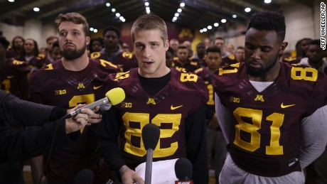 University of Minnesota wide receiver Drew Wolitarsky, flanked by quarterback Mitch Leidner, left, and tight end Duke Anyanwu stands in front of other team members as he reads a statement on behalf of the players in the Nagurski Football Complex in Minneapolis, Minn., Thursday night, Dec. 15, 2016.  The players delivered a defiant rebuke of the university's decision to suspend 10 of their teammates, saying they would not participate in any football activities until the school president and athletic director apologized and revoked the suspensions. If that meant they don't play in the upcoming Holiday Bowl against Washington State, they appeared poised to stand firm. (Jeff Wheeler/Star Tribune via AP)