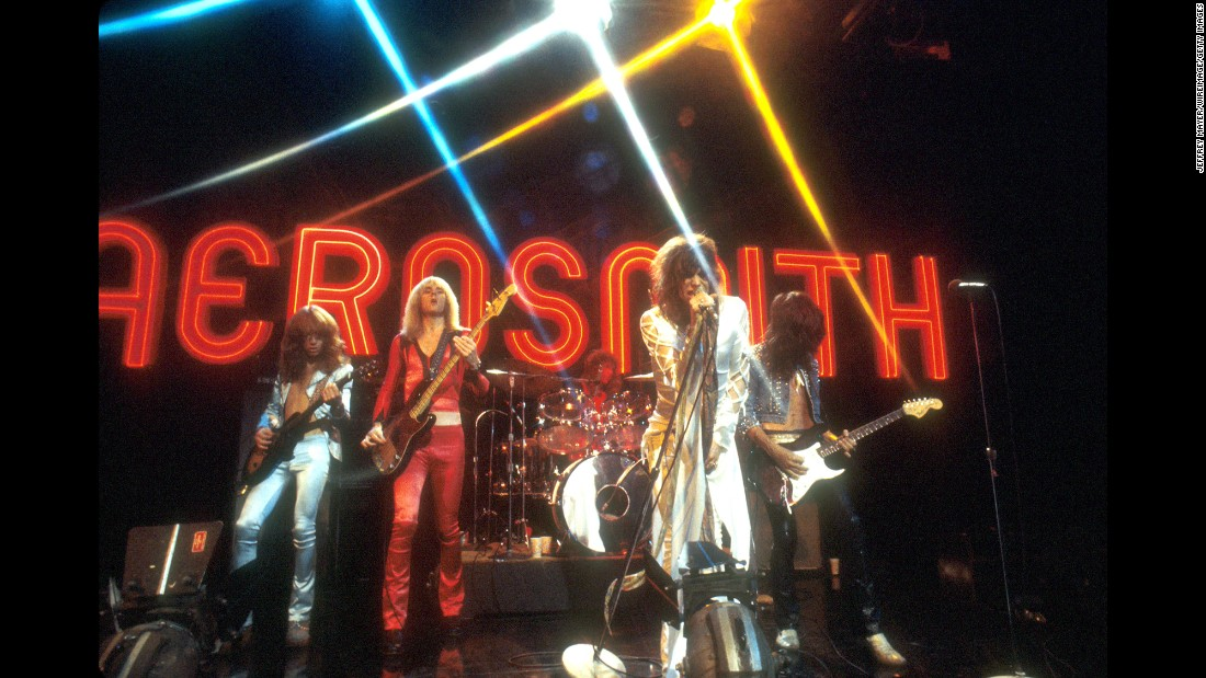 "These Rock and Roll Hall of Famers exploded out of Boston in the 1970s with popular album tracks like ""Dream On"" and ""Sweet Emotion."" Shown here during a 1974 performance on TV's ""Midnight Special,"" Aerosmith are (left to right) guitarist Brad Whitford, bassist Tom Hamilton, drummer Joey Kramer, singer/songwriter Steven Tyler and lead guitarist/songwriter Joe Perry. In 1986 they collaborated with Run-DMC, creating a groundbreaking rap/rock version of their hit, ""Walk This Way."" Later Aerosmith scored again with hit albums like ""Pump"" and ""Get a Grip.""  The band has sold 66.5 million units in the US, according to the Recording Industry Association of America."