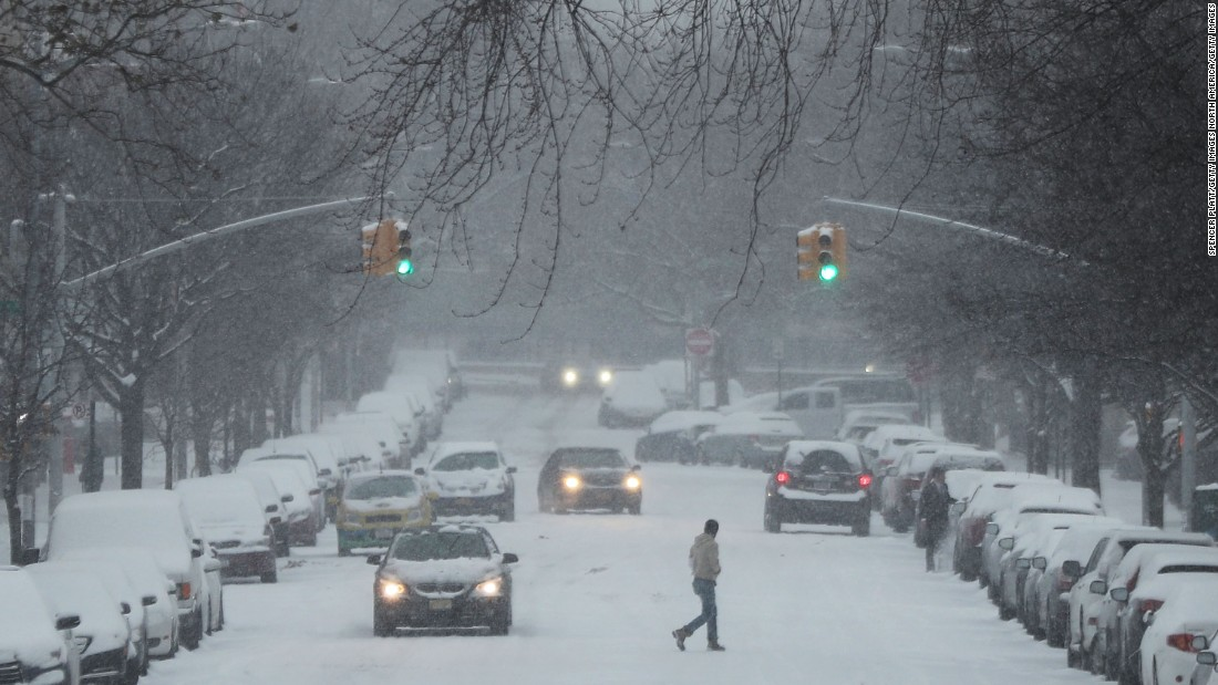 People walk through the snow along a Brooklyn street on December 17.