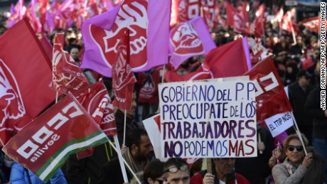 "Protestors hold flags and a banner reading, ""PP government, preoccupy yourselves with the workers. We can not do more"",  during a demonstartion called by the UGT and CCOO unions against poverty, pensions and unemployment, in Madrid on December 18, 2016. / AFP / JAVIER SORIANO        (Photo credit should read JAVIER SORIANO/AFP/Getty Images)"