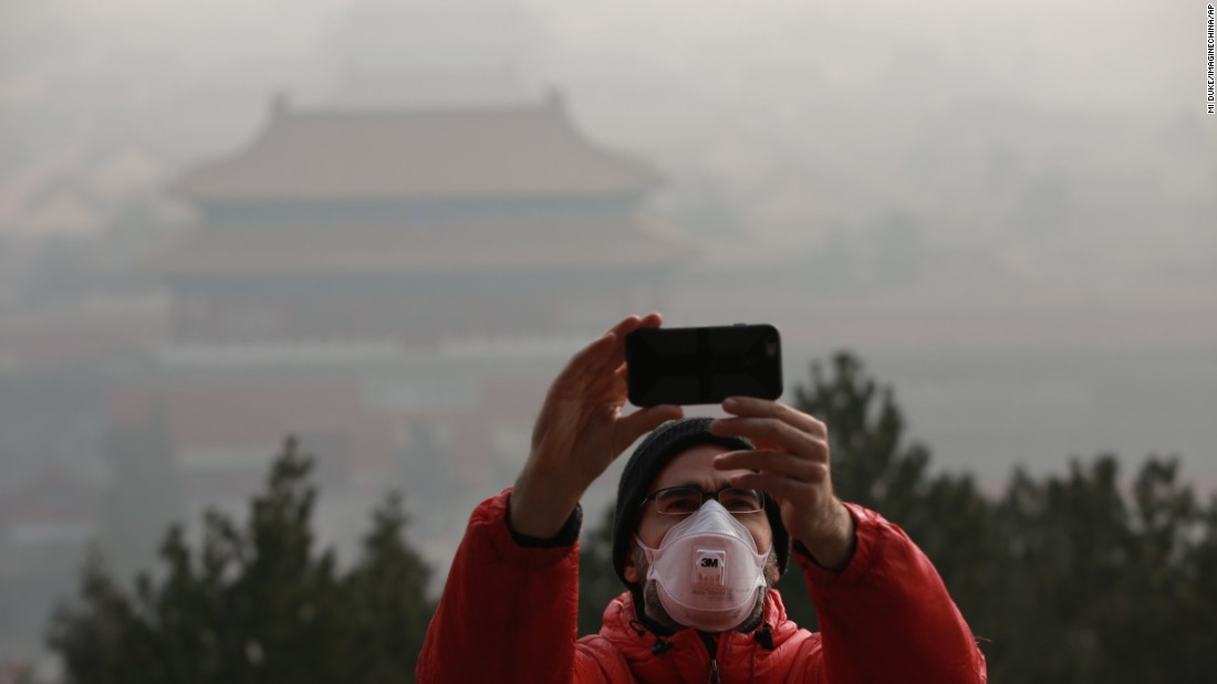 A tourist takes a selfie in Beijing on Saturday, December 17.