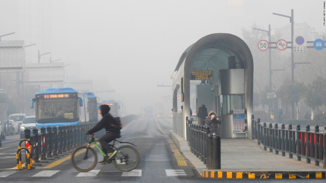 A cyclist crosses a smog-shrouded street in Lianyungang on December 19.