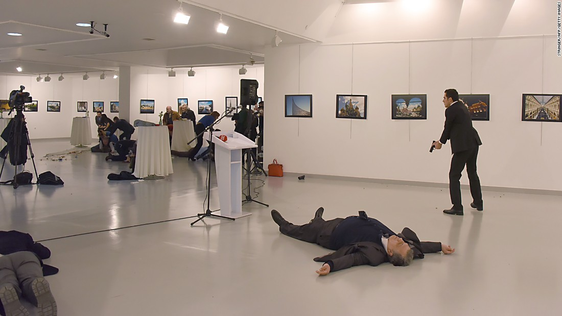 Karlov's body lies on the floor as the gunman stands nearby.