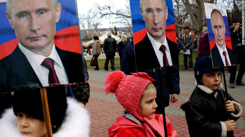 Children hold portraits of Russia's President Vladimir Putin as they take part in a rally to mark Defender of the Fatherland Day in the Crimean city of Sevastopol, on February 23, 2016.