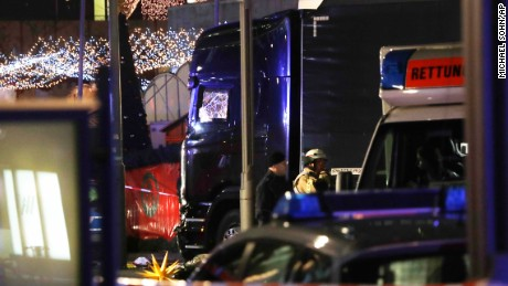 Police stand beside a damaged truck which ran into crowded Christmas market in Berlin, Germany, Monday, Dec. 19, 2016.