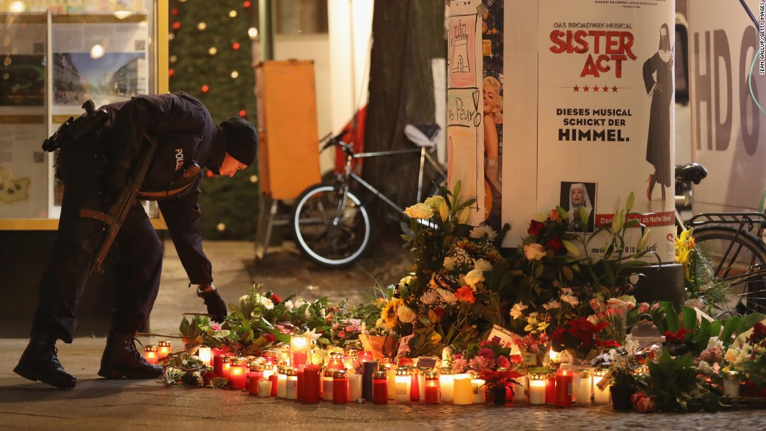 A police officer places a candle at a makeshift memorial in Berlin on December 20.