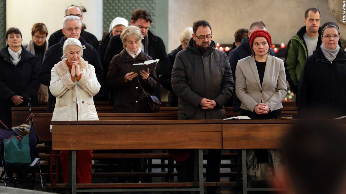 People attend a memorial service at St. Hedwig Cathedral in Berlin on December 20.