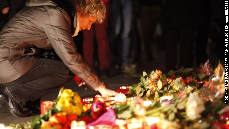 BERLIN, GERMANY - DECEMBER 20:  A woman leaves flowers and candles at the area the day after a lorry truck ploughed through a Christmas market on December 20, 2016 in Berlin, Germany. So far 12 people are confirmed dead and at least 48 injured. Authorities have confirmed they believe the incident was an attack and have arrested a Pakistani man who had fled immediately after the attack. Police are investigating the possibility that the truck, which belongs to a Polish trucking company, was stolen yesterday. (Photo by Michele Tantussi/Getty Images)