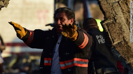 A fireman gestures to his colleagues as they work at the scene of the explosion.