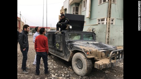 Civilians from Al-Barid neighborhood in eastern Mosul chat with a counterterrorism force member sitting on a CTF Humvee.