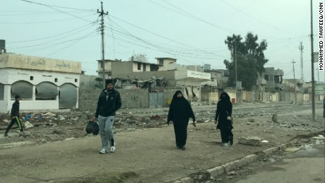 Residents walk in al-Samah neighborhood in liberated areas in eastern Mosul. Many women were seen uncovering their faces, one of many things they could not do under the control of ISIS.