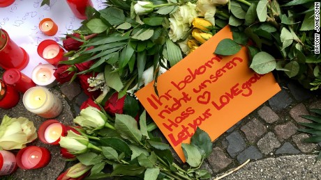 "People leave tributes to the Berlin victims. One note reads, ""Let your love grow."""