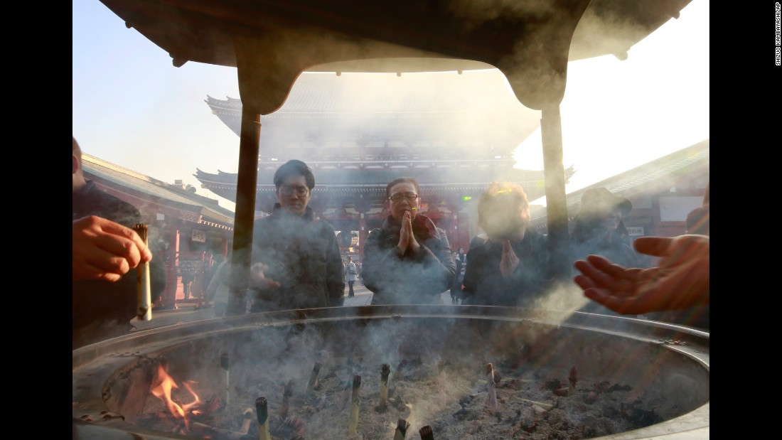 Worshippers gather around a huge incense burner as they pray at a Buddhist temple in Tokyo on Tuesday, December 20.