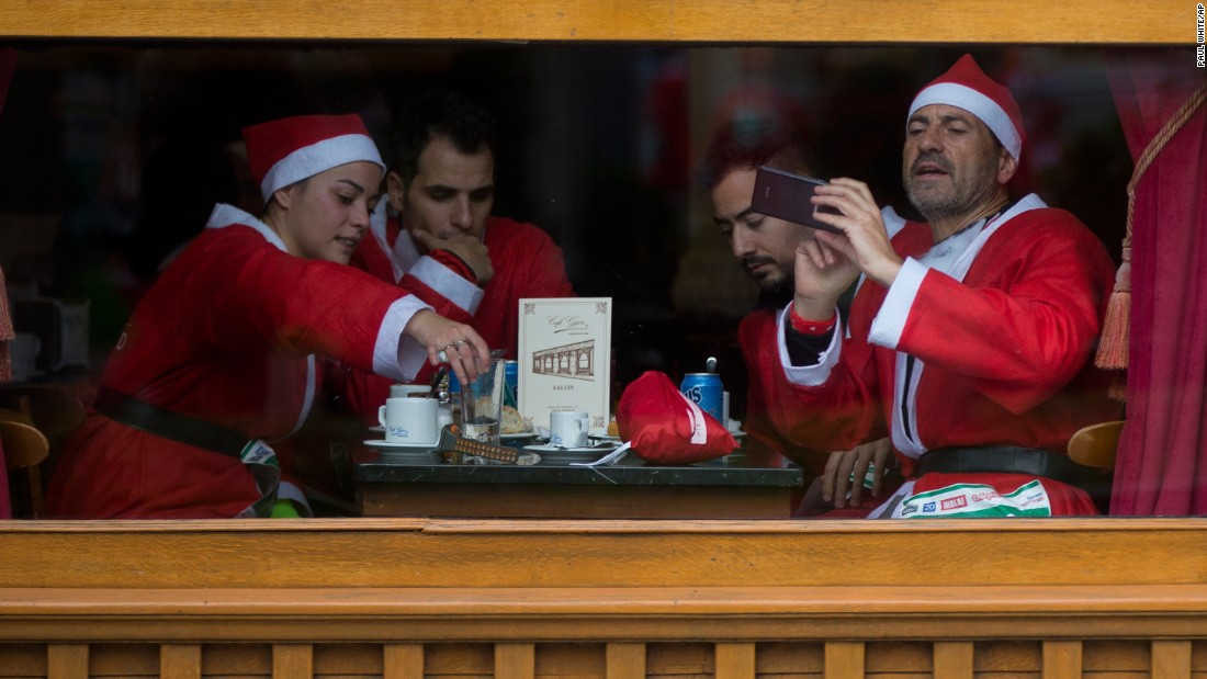 People dressed in Santa Claus costumes sit in a Madrid bar after taking part in a Santa run on Saturday, December 17.