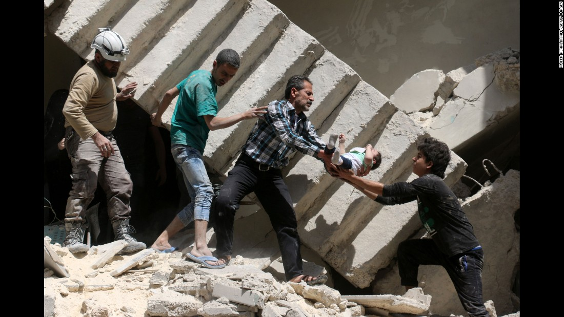 Syrian civil defense volunteers and rescuers remove a baby from under the rubble of a destroyed building after a reported airstrike on the rebel-held neighborhood of al-Kalasa in Aleppo on April 28, 2016.