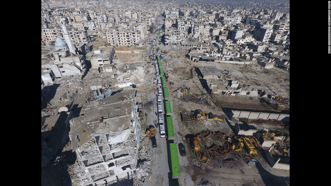 An aerial view shows a convoy of buses and ambulances waiting at a crossing point in the Amiriyah district of Aleppo on December 15, 2016, to evacuate civilians trying to flee from areas under siege by Iran-led Shiite militias and Assad regime forces.