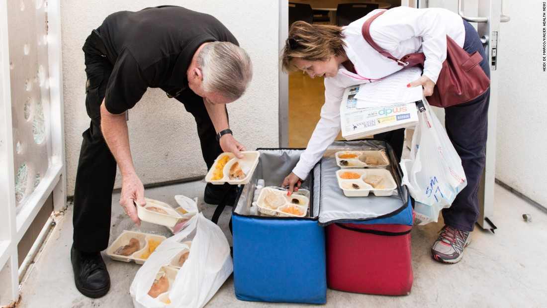Volunteers Mike and Kathy Kearin sort through the hot and frozen meals before delivering them to 14 residents at an apartment building in Venice, California.