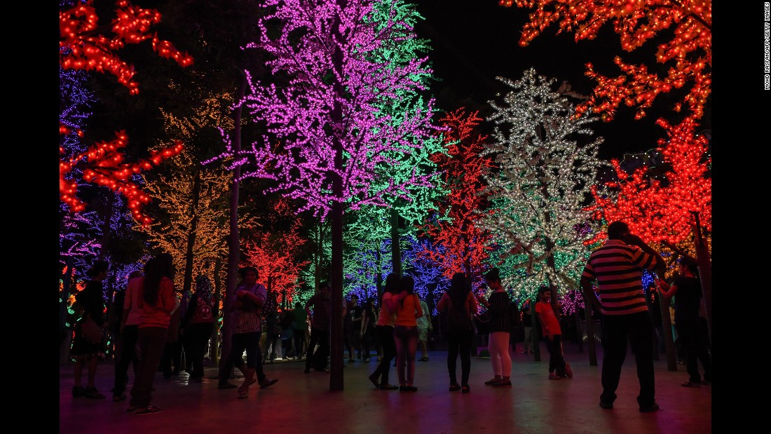 Visitors take pictures of Christmas trees illuminated by LED lights on Christmas Eve in Shah Alam, outside Kuala Lumpur, Malaysia.