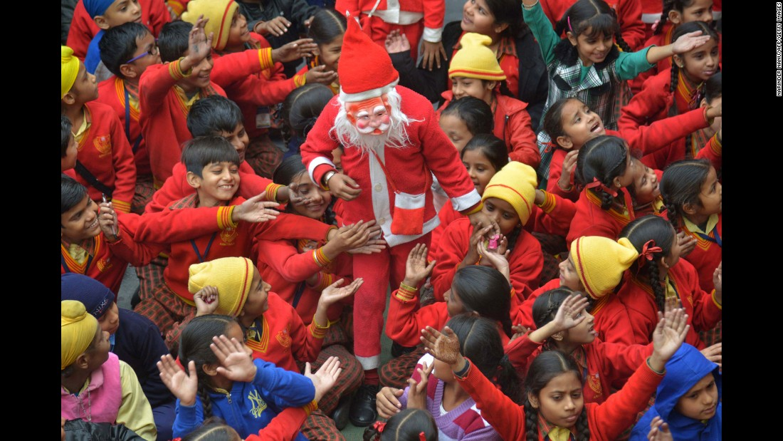 An Indian schoolboy wearing a Santa Claus outfit is surrounded by classmates as he gives out sweets during Christmas celebrations at a school in Amritsar on Christmas Eve.