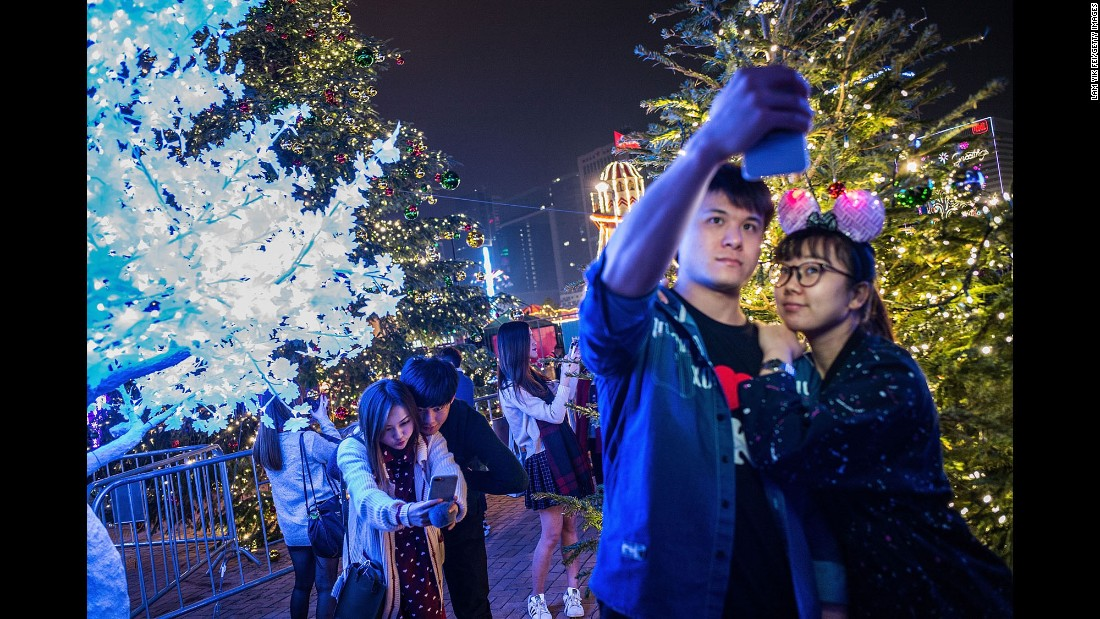 Couples take selfies in front of holiday decorations at shopping area on December 24, in Hong Kong.