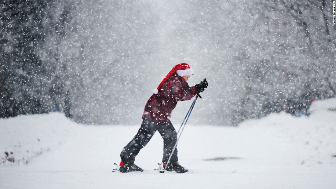 A boy wearing a Santa hat skis along a street near Montreal, Canada on December 24.
