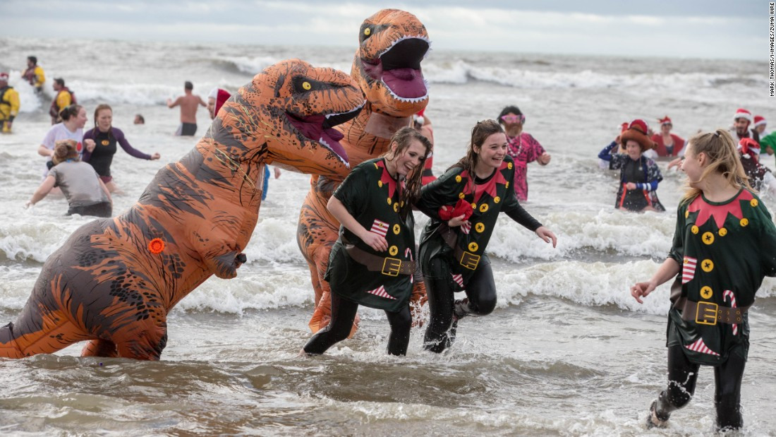 Participants dressed as dinosaurs and in festive clothing join in the Christmas Day 'Fancy Dress' swim in Dorset, England, to raise money for charity.