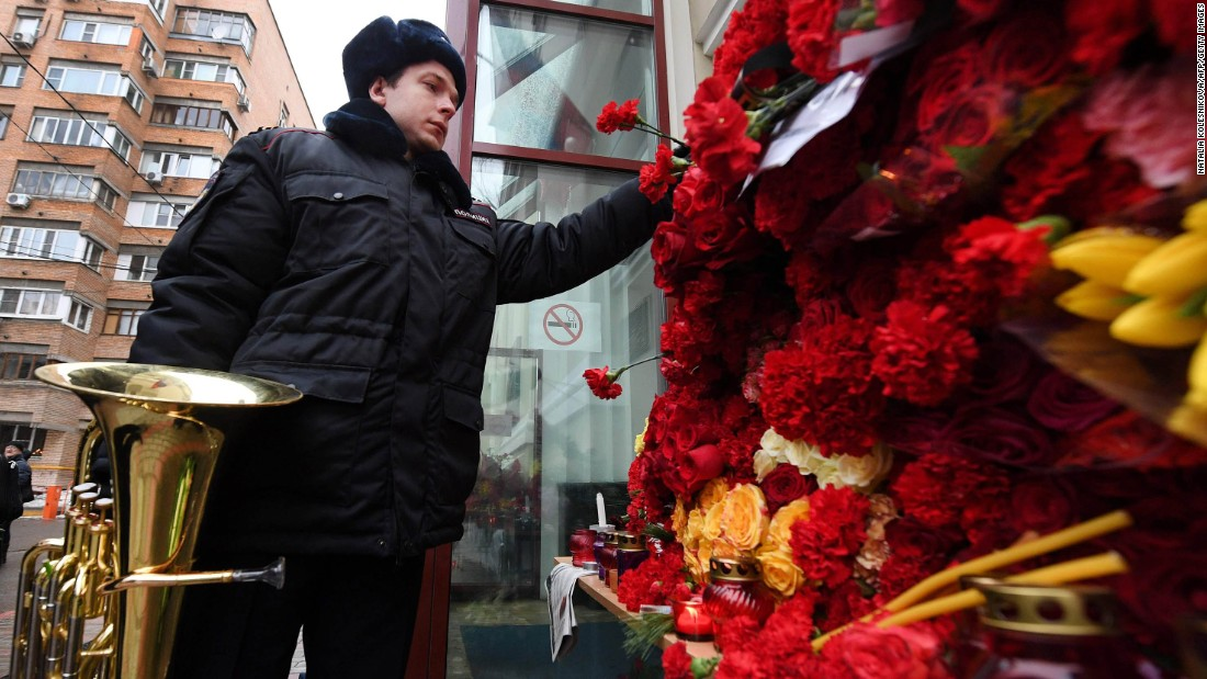 A Russian police orchestra musician places a flower in tribute to members of the Alexandrov Ensemble outside their home stage building in Moscow on December 26. The popular ensemble was scheduled to perform for Russian pilots in Syria ahead of New Year's Day.