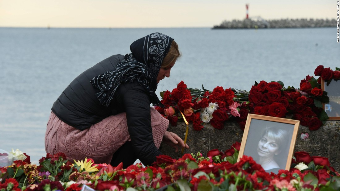 A woman lights a candle Tuesday next to makeshift memorial in Sochi, Russia, for  Russian activist Elizaveta Glinka, who was killed in the crash. Also presumed dead were nine journalists and more than 60 members of the Russian army's official choir, the Alexandrov Ensemble.