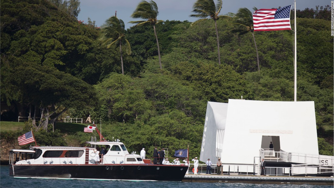 A boat carrying Obama and Abe arrives at the USS Arizona Memorial.