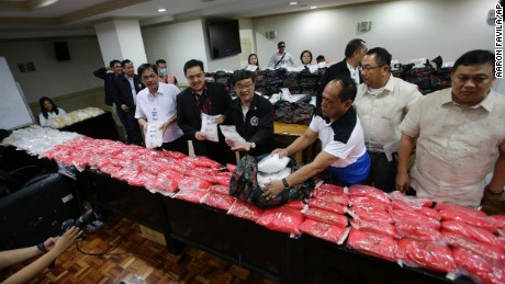 Philippine Justice Secretary Vitaliano Aguirre II, center, and National Bureau of Investigation Director Dante Gierran, 3rd from right, display nearly one metric ton of seized methamphetamine during a press conference in Manila, Philippines Tuesday, Dec. 27, 2016. Aguirre II said Tuesday the 890 kilograms (1,962 pounds) of methamphetamine seized in the series of raids that started on Dec. 1 until Dec. 26 has a street value of nearly 6 billion pesos ($120 million), the biggest drug haul in the country so far. 10 people including 3 Chinese nationals were arrested during the raids. (AP Photo/Aaron Favila)