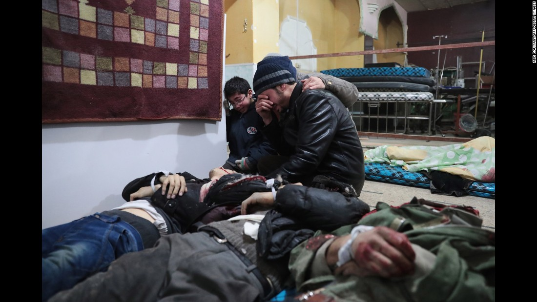 Syrian men mourn over the body of a relative at a makeshift hospital in the rebel-held town of Douma, on the eastern outskirts of Damascus, following reported air strikes on Thursday, December 29.