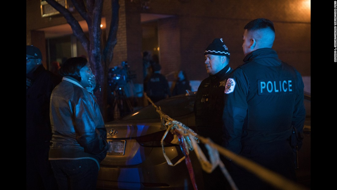 "A woman talks with members of the Chicago Police Department at the <a href=""http://www.cnn.com/2016/12/26/us/chicago-christmas-homicides/"" target=""_blank"">scene of a shooting</a> on Sunday, December 25, in Chicago. <br />"