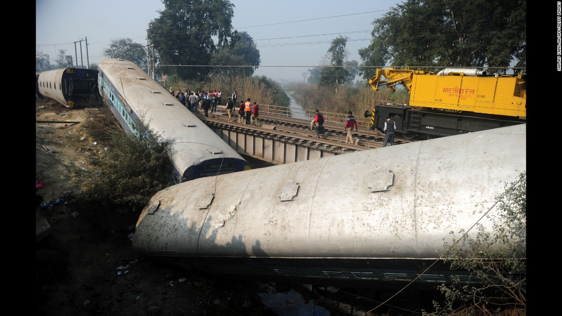 Indian officials and bystanders gather beside the wreckage of train carriages on Wednesday, December 28, following a train crash in the northern Indian state of Uttar Pradesh. At least two people died and 28 were injured after a train derailed near the site of a previous rail accident.