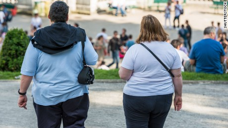 An obese couple walk in a park near Montmartre, in Paris, France.