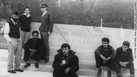 1960:  A photograph taken by John Lennon showing an early incarnation of the Beatles sitting in front of the inscription 'Their Name Liveth For Evermore', at the Arnhem War Memorial in the eastern Netherlands; (left to right) Beatles manager Allan Williams, his wife Beryl, Williams' business partner and black Calypso singer Lord Woodbine, Stuart Sutcliffe, Paul McCartney, George Harrison (1943 - 2001) and Pete Best.  (Photo by John Lennon/Keystone Features/Getty Images)