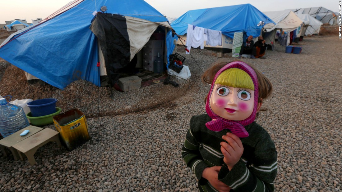 An Iraqi girl who fled the violence in Mosul, Iraq, poses with a mask on New Year's Eve at the Hasansham camp in northern Iraq.