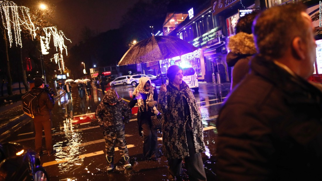 People walk in the rain near the scene of the attack.