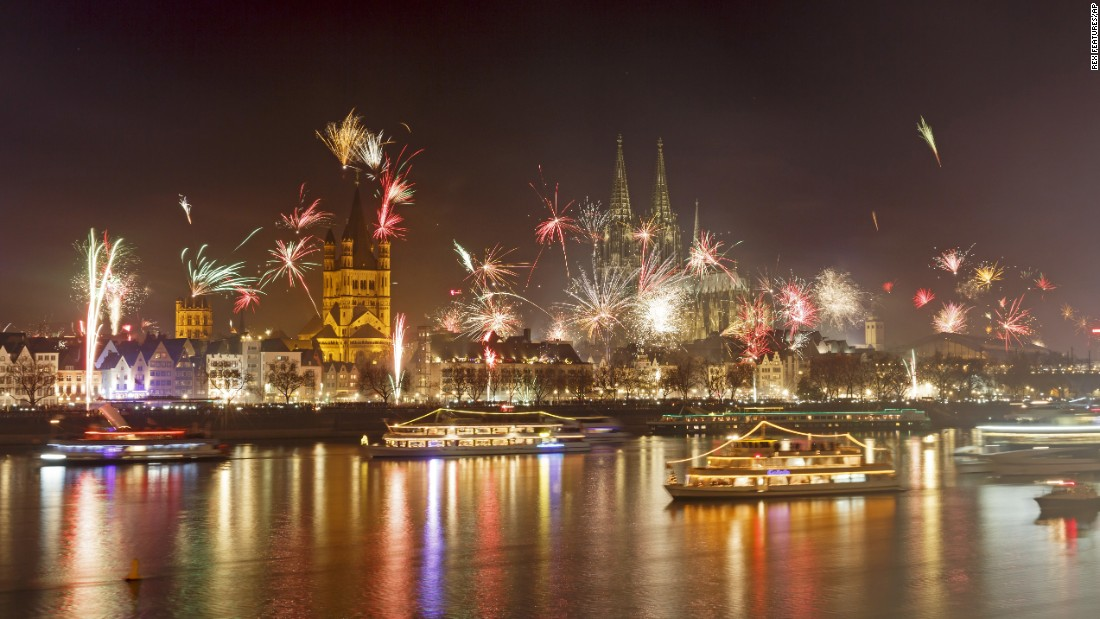 Fireworks illuminate the night sky over Cologne Cathedral and the Rhine River during New Year's Eve celebrations in Cologne, Germany.